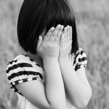 Jeune fille malheureuse cachant son visage avec ses mains